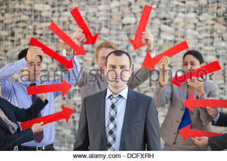 Group of business people pointing arrows towards businessman - Stock Photo