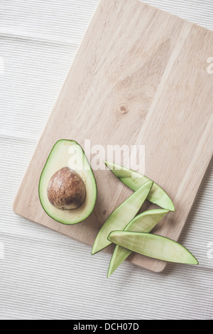 Avocado cut in half with stone - Stock Photo