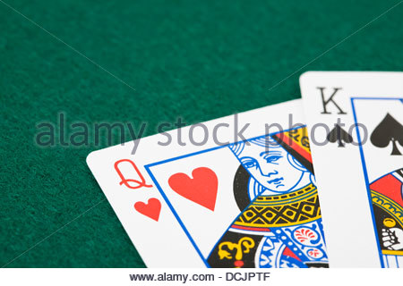 Closeup of queen of hearts and king of spades playing cards over green felt surface - Stock Photo