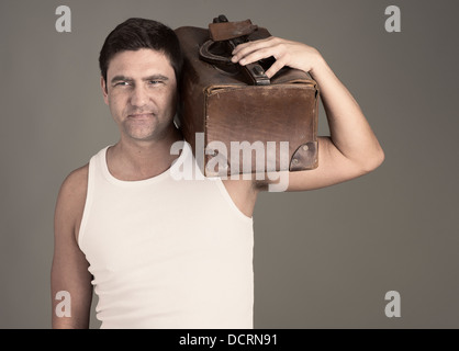 Determined man in white tank top holding brown leather luggage bag on his shoulder - Stock Photo