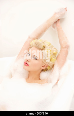 Young Woman in Hair Rollers Having a Bath - Stock Photo