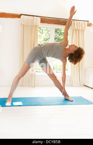Woman Practicing Yoga in the Triangle Pose - Stock Photo
