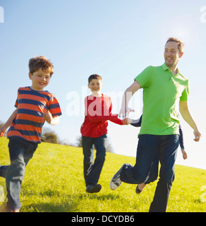 Father and Sons Running on Field - Stock Photo