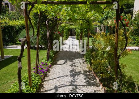 View of ornamental garden , with arbour, surrounded by vines, path lined with flowers, and grass lawns, Renaissance - Stock Photo
