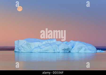 Iceberg at Sunset and Moonrise at Hall Bredning, Scoresby sund, Greenland - Stock Photo