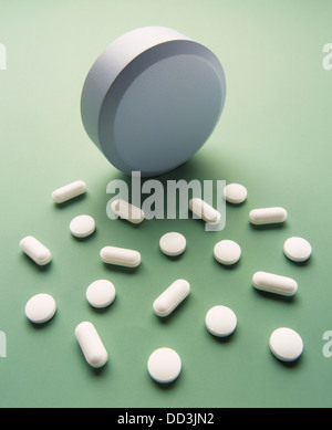 A large white tablet with many smaller capsules and pills. Light green background - Stock Photo