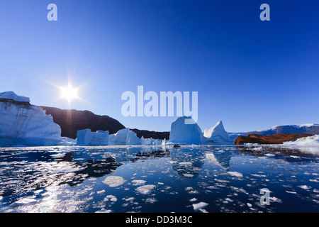 Cruising between the icebergs at Røde Ø, Scoresby sund, Greenland - Stock Photo