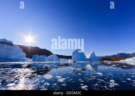 Cruising between the icebergs at Røde Ø, Scoresby sund, Greenland - Stock Photo