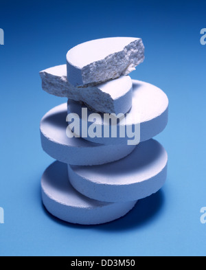 A large stack of white medicine tablets on a blue background. - Stock Photo
