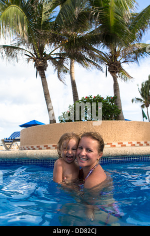 Mother and daughter having great time in the swimming pool under the palm trees - Stock Photo