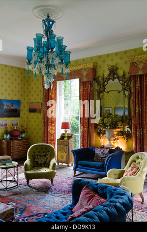 Sitting room wallpaper by Cole & Sons with contrasting blue upholstery and cherry red chintz curtains - Stock Photo