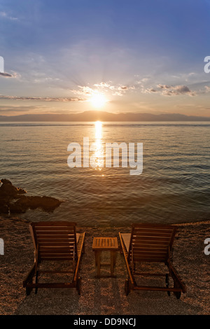 Croatia, Krk, Sunbeds at sunset in Njivice - Stock Photo
