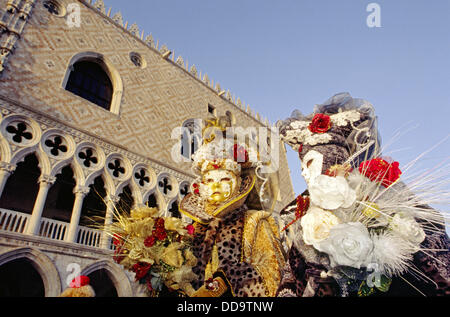 Two people at San Marco dressed in lavish colourful costumes for a masquerade at Carnival. Venice, Italy - Stock Photo