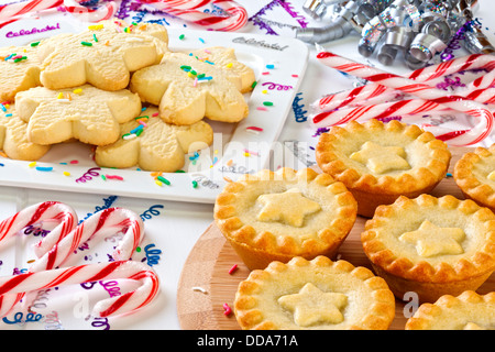 A buffet table set up for a celebration, with Christmas fruit mince pies, star shaped shortbread with sprinkles... - Stock Photo