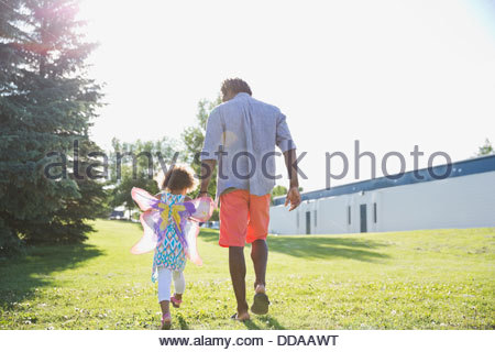 Rear view of father and daughter walking at park - Stock Photo