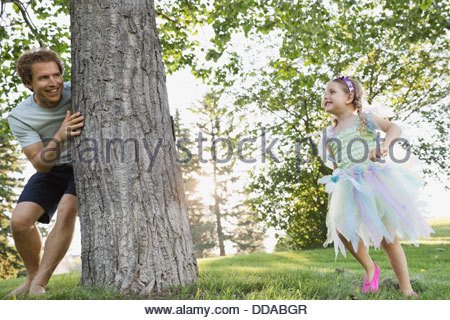 Father and daughter playing hide and seek in park - Stock Photo