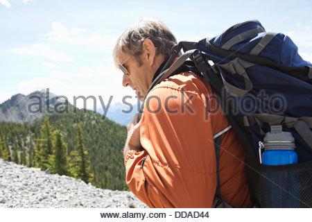 Mature man hiking on mountain - Stock Photo