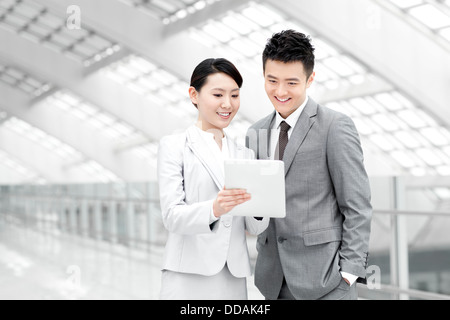 Business colleagues with digital tablet talking in airport lobby - Stock Photo