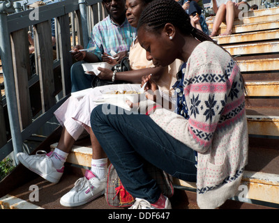 A teen with her parents enjoying food from the street market at the South Bank London UK   KATHY DEWITT - Stock Photo