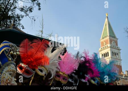 Traditional Venetian masks with feathers by the Bell Tower on Piazza San Marco, Venice, Italy - Stock Photo