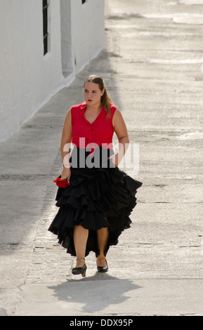 Woman in a traditional flamenco dress walking in an andalusian village. Mijas Pueblo in Southern Spain. Costa del - Stock Photo