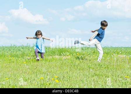 Children running in field with arms out - Stock Photo