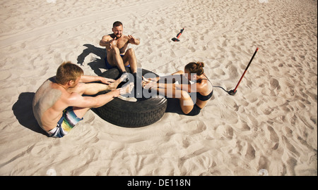 Fitness and healthy lifestyle. Small group of young athletes doing abdominal exercise with a truck tire on beach. - Stock Photo