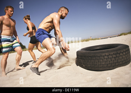Strong male athlete about to flip a truck tire. Young people doing crossfit exercise on beach on a sunny day. - Stock Photo