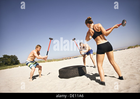 Three strong athletes doing hammer strike on a truck tire during crossfit exercise outside on beach - Stock Photo