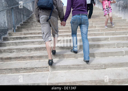 Young couple going up the stairs together, hand in hand, from behind - Stock Photo