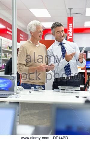 Salesman showing senior man digital tablet in electronics store - Stock Photo