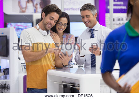 Salesman showing couple digital tablets in electronics store - Stock Photo