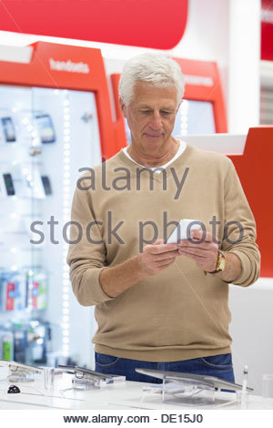 Senior man looking at cell phone in electronics store - Stock Photo