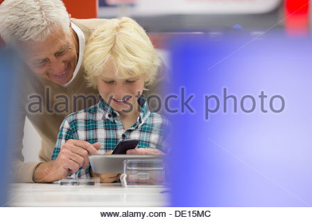 Smiling grandfather and grandson looking at cell phone and digital tablet in electronics store - Stock Photo