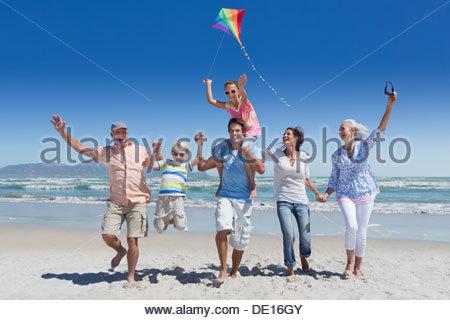 Happy multi-generation family with kite running and waving on sunny beach - Stock Photo