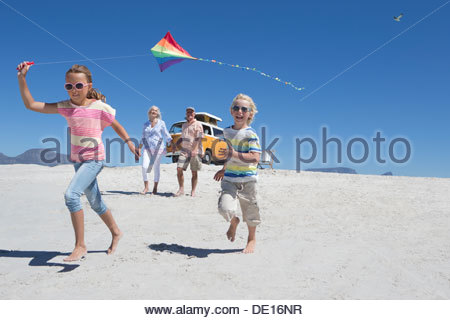 Grandparents and grandchildren running with kite on sunny beach with van in background - Stock Photo