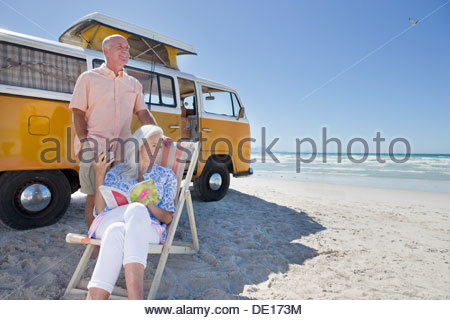 Senior couple relaxing outside van on sunny beach - Stock Photo