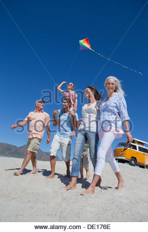 Happy multi-generation family with kite walking on sunny beach with van in background - Stock Photo