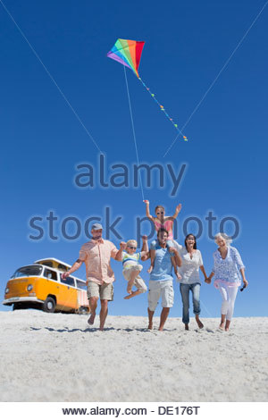 Happy multi-generation family with kite walking on sunny beach with van in background - Stockfoto