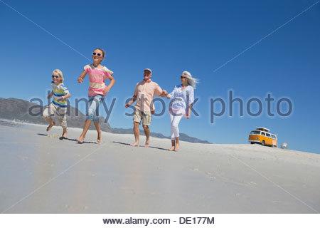 Grandparents and grandchildren running on sunny beach with van in background - Stock Photo
