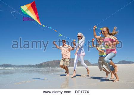 Grandparents and grandchildren running on sunny beach - Stock Photo