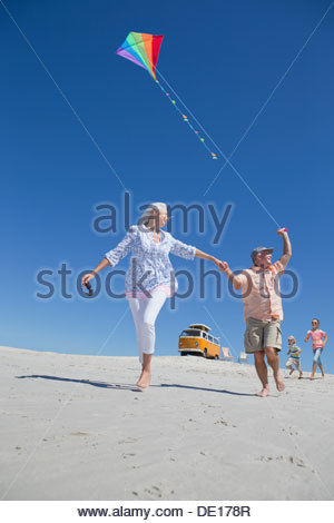 Grandparents and grandchildren with kite running on sunny beach with van in background - Stock Photo