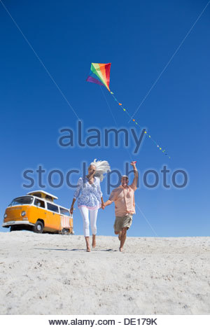Happy senior couple running with kite on sunny beach with van in background - Stock Photo