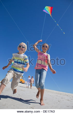 Boy and girl with kite running on sunny beach - Stock Photo