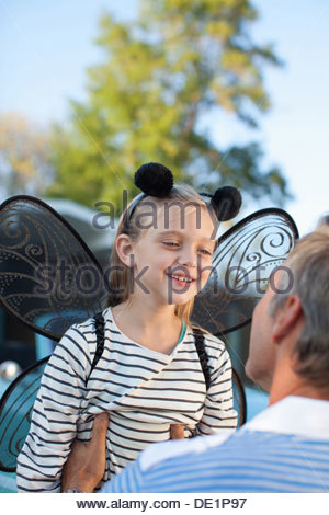 Father hugging daughter in fairy wings - Stockfoto