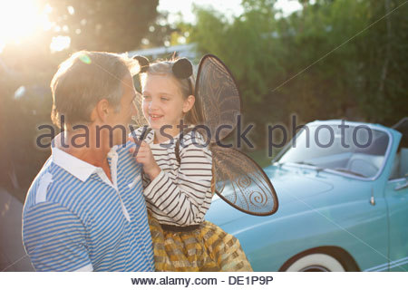 Father holding daughter in fairy wings - Stockfoto