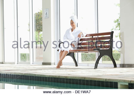 Portrait of smiling woman in bathrobe sitting on bench poolside at spa - Stock Photo