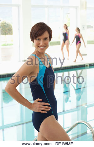 Portrait of smiling women sitting at edge of swimming pool - Stock Photo