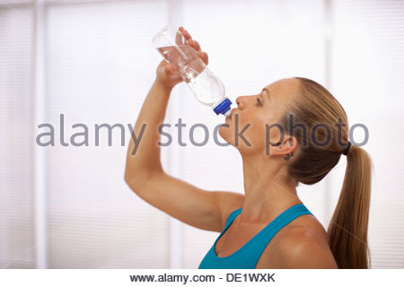 Woman in sports bra drinking water - Stock Photo