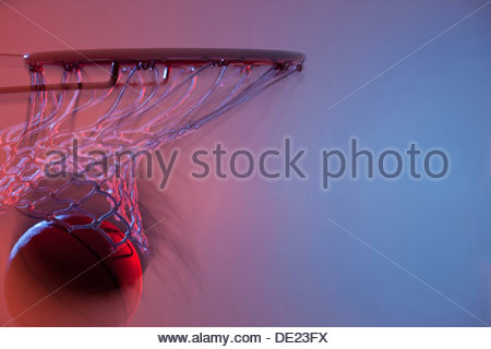 Blurred view of basketball going into hoop - Stock Photo